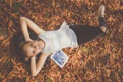Девушка лежит вниз с цифровой таблеткой внешней Стоковое Фото