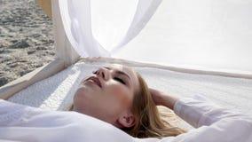 Девушка лежит в белом занавесе, молодой женщине на пляже, экзотическом плодоовощ, сток-видео