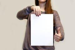 Девушка держа белый чистый лист бумаги A4 вертикально и большие пальцы руки вверх Лист Стоковая Фотография