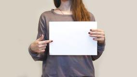 Девушка держа белый чистый лист бумаги A4 вертикально Presentati листовки Стоковое Изображение RF