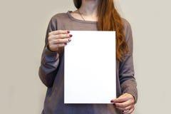 Девушка держа белый чистый лист бумаги A4 вертикально Presentati листовки Стоковые Фото