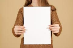 Девушка держа белый чистый лист бумаги A4 вертикально Presentati листовки Стоковое фото RF