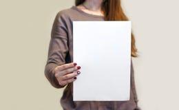 Девушка держа белый чистый лист бумаги A4 вертикально Presentati листовки Стоковая Фотография