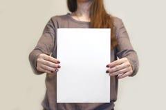 Девушка держа белый чистый лист бумаги A4 вертикально Presentati листовки Стоковая Фотография RF