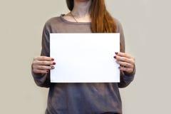 Девушка держа белый чистый лист бумаги A4 вертикально Presentati листовки Стоковые Изображения
