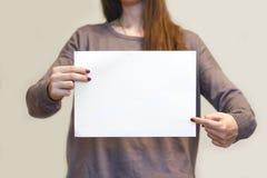 Девушка держа белый чистый лист бумаги A4 горизонтально Presenta листовки Стоковое Фото