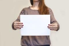 Девушка держа белый чистый лист бумаги A4 горизонтально Presenta листовки Стоковые Фотографии RF