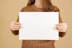 Девушка держа белый чистый лист бумаги горизонтально Presentatio листовки Стоковое Фото