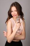 Девушка держа бокал воды конец вверх Серая предпосылка Стоковая Фотография