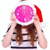 Девушка держа большие часы в шляпе рождества на его стороне стоковое фото