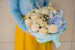 Девушка держа букет белого и голубого цветка Стоковое Фото