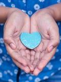 Девушка держа деревянную форму сердца Стоковые Изображения