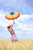 Девушка держа зонтик и положение шляпы поднимая внутри Стоковые Фото