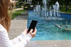 Девушка держа конец-вверх телефона рук Стоковые Фото