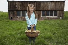 Девушка держа корзину яичка на ферме Стоковое Изображение