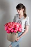Девушка держа красивый коралл смешивания и розовый букет цветка в круглой коробке с крышкой коралл Sharm ранга пионов Стоковые Фотографии RF