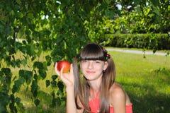 Девушка держа красное яблоко в ее руке Стоковые Фотографии RF
