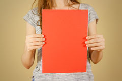 Девушка держа красный чистый лист бумаги A4 вертикально Представление листовки Стоковые Фото