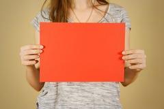 Девушка держа красный чистый лист бумаги A4 горизонтально Presentati листовки Стоковое Изображение