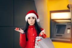 Девушка держа малые подарочную коробку и хозяйственные сумки перед ATM Стоковые Фотографии RF
