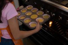 Девушка держа олово булочки в печи на кухне Стоковые Изображения