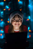 Девушка держа ПК таблетки в шляпе ` s Санты Стоковая Фотография RF