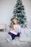 Девушка держа подарочную коробку около рождественской елки Ребенк раскрывая настоящий момент Xmas Стоковая Фотография RF