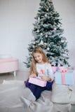 Девушка держа подарочную коробку около рождественской елки Ребенк раскрывая настоящий момент Xmas Стоковые Изображения