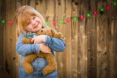Девушка держа плюшевый медвежонка перед лесистой предпосылкой с Крисом стоковое фото rf