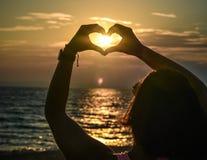 Девушка держа руки в форме сердца на пляже Стоковые Изображения