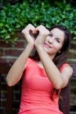 Девушка держа руки в форме сердца Стоковые Изображения RF
