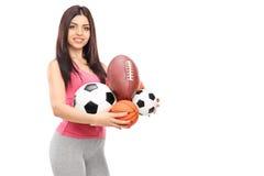 Девушка держа серии различного вида шариков спорт Стоковое Фото