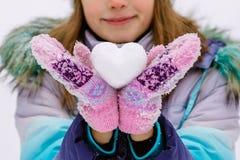 Девушка держа сердце сделанный снега стоковые фото