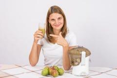 Девушка держа стекло свежих сока и пунктов к нему Стоковые Изображения