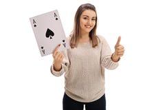 Девушка держа туз карточки лопат и давая большой палец руки вверх Стоковое Изображение RF