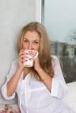 Девушка держа чашку и смотря через окно Стоковое Фото