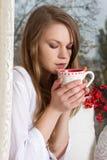 Девушка держа чашку и смотря через окно Стоковые Фотографии RF