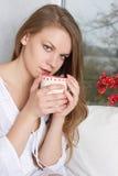 Девушка держа чашку и смотря через окно Стоковые Изображения RF