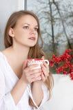 Девушка держа чашку и смотря через окно Стоковое Изображение
