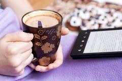 Девушка держа чашку кофе и читая ebook Стоковое Фото