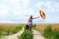Девушка держа чемодан и зонтик стоя дальше Стоковое Фото