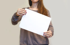 Девушка держа aslant белый чистый лист бумаги A4 вертикально Листовка pre Стоковая Фотография