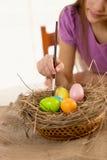 Девушка держа paintbrush и крася пасхальные яйца Стоковое фото RF