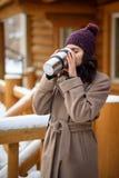 Девушка держа thermos с горячим питьем Кружка кофе в ее руках Переулок зимы в городе, маленькая девочка идет Стоковое Изображение