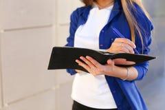 Девушка держит в руках дневнике, тетради с листами и ручке и исковом заявлении стоковая фотография rf