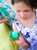 Девушка держит ее покрашенное зеленое пасхальное яйцо Стоковое Фото