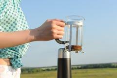 Девушка держит прессу прессы с кофе на предпосылке ландшафта сельской местности лета Конец-вверх Стоковая Фотография RF