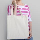 Девушка держит пустую сумку eco хлопка, модель-макет дизайна Стоковое Фото