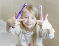 Девушка держит 2 различных зубной щетки в ее руках Стоковая Фотография