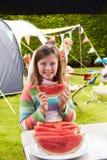 Девушка есть арбуз пока на празднике семьи располагаясь лагерем стоковое изображение